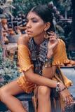 La bella giovane donna alla moda con compone ed accessori alla moda di boho che posano sul fondo tropicale fotografia stock