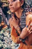 La bella giovane donna alla moda con compone ed accessori alla moda di boho che posano sul fondo tropicale naturale fotografia stock libera da diritti