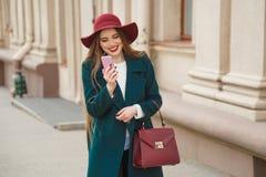 La bella giovane donna alla moda vestita riceve una telefonata fotografie stock