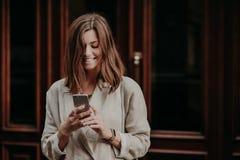 La bella giovane donna allegra riceve il messaggio di notifica, ottiene l'offerta di pubblicità, fa vestirsi il taglio di capelli immagine stock