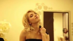 La bella giovane donna applica la polvere e la base per trucco perfetto sul suo fronte stock footage