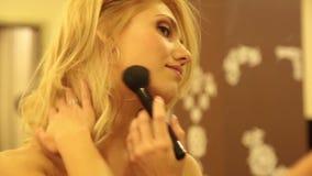 La bella giovane donna applica la polvere e la base per trucco perfetto sul suo fronte archivi video