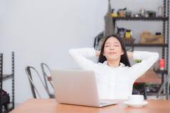 La bella giovane donna asiatica con l'allungamento del computer portatile e l'esercizio si rilassano dopo successo del lavoro Fotografia Stock Libera da Diritti