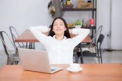 La bella giovane donna asiatica con l'allungamento del computer portatile e l'esercizio si rilassano dopo successo del lavoro Fotografia Stock