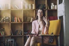 La bella giovane donna astuta si siede con il libro elettronico in Immagini Stock Libere da Diritti