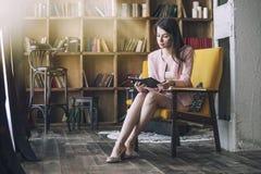 La bella giovane donna astuta si siede con il libro elettronico in Fotografie Stock