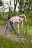 La bella giovane donna bionda che fa il lato piega su un sentiero per pedoni della foresta Fotografia Stock Libera da Diritti
