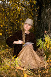 La bella giovane donna bionda che si siede all'aperto negli ultimi raggi di sole al tramonto di autunno dipinge uno schizzo in bl Fotografie Stock Libere da Diritti