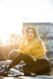 La bella giovane donna bionda sexy che assomiglia a Jennifer Aniston sta sedendosi in pallet di legno di rovine Fotografie Stock Libere da Diritti