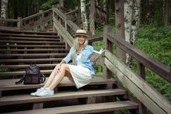 La bella giovane donna bionda si siede sui punti di legno in un parco della città con un libro in mani Sta portando un vestito bi Fotografie Stock Libere da Diritti