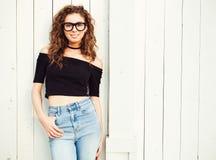 La bella giovane donna castana con capelli lunghi si è vestita in cima e jeans che posano nello stile 70 su una sera calda dell'e Immagini Stock Libere da Diritti