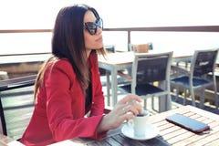 La bella giovane donna che beve il latte del tè verde di Matcha sopra wodden la tavola nella caffetteria immagine stock