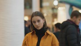 La bella giovane donna compare dalla folla che il suo sguardo è vi ferma per tormentare l'effetto di focalizzazione al suo fronte stock footage