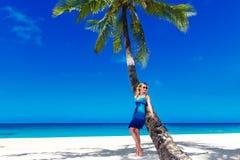 La bella giovane donna con capelli biondi lunghi si rilassa sulla palma Fotografia Stock Libera da Diritti