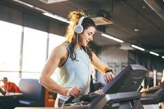 La bella giovane donna con capelli lunghi si prepara nella palestra su una pedana mobile Ascolta musica in grandi cuffie Sul suo  fotografie stock libere da diritti