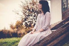 La bella giovane donna con capelli scuri che si siedono sui punti si avvicina alla t Fotografie Stock