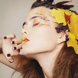 La bella giovane donna con l'autunno compone la posa nello studio più Fotografie Stock