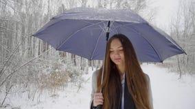 La bella giovane donna con l'ombrello sta camminando all'aperto in un parco dell'inverno Movimento lento Ritratto alla moda di in video d archivio