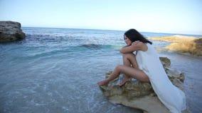 La bella giovane donna con le labbra rosse luminose si siede sulla spiaggia archivi video