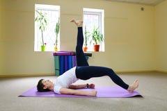 La bella giovane donna con moro si esercita di yoga Immagini Stock