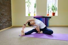 La bella giovane donna con moro si esercita di yoga Fotografia Stock