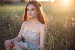 La bella giovane donna con perfetto compone e capelli lungamente intrecciati che si siedono nel campo al tramonto immagine stock