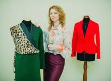 La bella giovane donna cuce il cappotto del progettista Cappotto e verde della stampa del leopardo fotografia stock libera da diritti