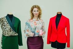 La bella giovane donna cuce il cappotto del progettista Cappotto e verde della stampa del leopardo immagini stock