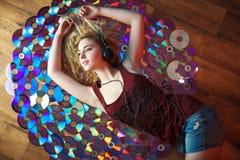 La bella giovane donna in cuffie si diverte ed ascolta musica Fotografia Stock