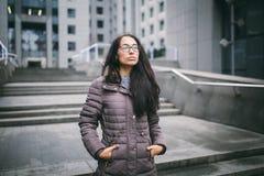 La bella giovane donna di etnia europea con capelli castana lunghi, vetri d'uso e un cappotto sta contro il contesto di un busin fotografia stock