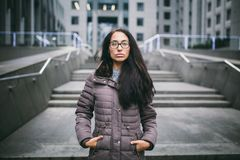 La bella giovane donna di etnia europea con capelli castana lunghi, vetri d'uso e un cappotto sta contro il contesto di un busin fotografia stock libera da diritti