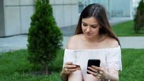 La bella giovane donna fa gli acquisti online facendo uso del telefono, entra in un numero di carta di credito che si siede sull' video d archivio