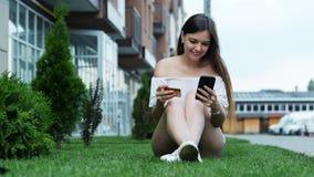 La bella giovane donna fa gli acquisti online tramite il telefono, entra in un numero di carta di credito che si siede sull'erba  stock footage