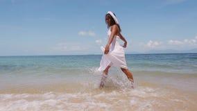 La bella giovane donna felice in una corona bianca del fiore e del vestito funziona a piedi nudi lungo il litorale nel mare e god stock footage