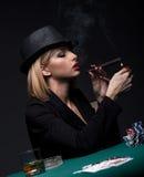 La bella giovane donna fuma un sigaro durante il gioco del poker Immagine Stock