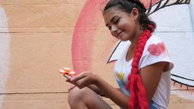 La bella giovane donna giocata dal filatore sulla via, giocattolo moderno per distensione della tensione gira sul dito femminile  video d archivio