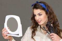 La bella giovane donna guarda in uno specchio Immagini Stock
