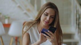 La bella giovane donna ha le attività bancarie online ed acquisto facendo uso dello smartphone e della carta di credito a casa stock footage