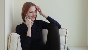 La bella giovane donna legge un libro ed i colloqui dal telefono mentre si siede al davanzale a casa stock footage