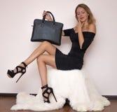 La bella giovane donna lussuosa in un vestito nero si siede su una copertura bianca della pelliccia in sandali alla moda neri ed  immagine stock