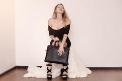 La bella giovane donna lussuosa in un vestito nero si siede su una copertura bianca della pelliccia in sandali alla moda neri ed  fotografia stock libera da diritti