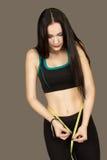 La bella giovane donna misura in abiti sportivi a se stessa il wais Fotografia Stock