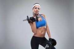 La bella giovane donna pareggiante si esercita con le teste di legno isolate Fotografia Stock