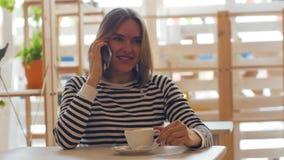 La bella giovane donna parla sul telefono e sul sorridere stock footage