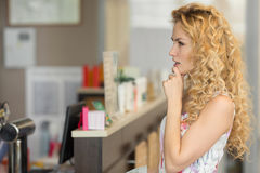 La bella giovane donna pensa che cosa comprare in caffè Fotografie Stock