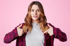 La bella giovane donna positiva con il sorriso piacevole, indica allo spazio in bianco della copia dei vestiti per la vostra prog Fotografie Stock