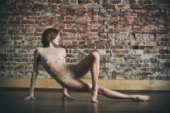 La bella giovane donna pratica il asana di yoga allo studio di yoga su un fondo del muro di mattoni Immagini Stock