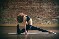 La bella giovane donna pratica il asana di yoga allo studio di yoga su un fondo del muro di mattoni Fotografia Stock Libera da Diritti