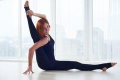 La bella giovane donna pratica il asana Parivritta Kraunchasana di yoga allo studio di yoga Fotografia Stock