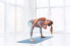 La bella giovane donna pratica il asana Parivritta Stupasana di yoga alla classe di yoga fotografia stock libera da diritti